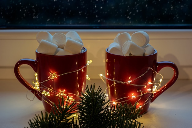 Red mugs with hot chocolate and marshmallow with christmas lights and falling snow outside the window, christmas holidyas