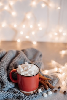 Red mugs with hot chocolate and marshmallows and gingerbread cookies.