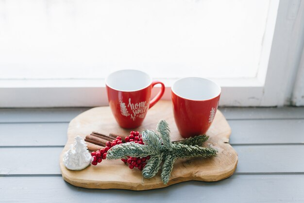 Red mugs with tea, coffee or mulled wine on the windowsill in the decor of a house
