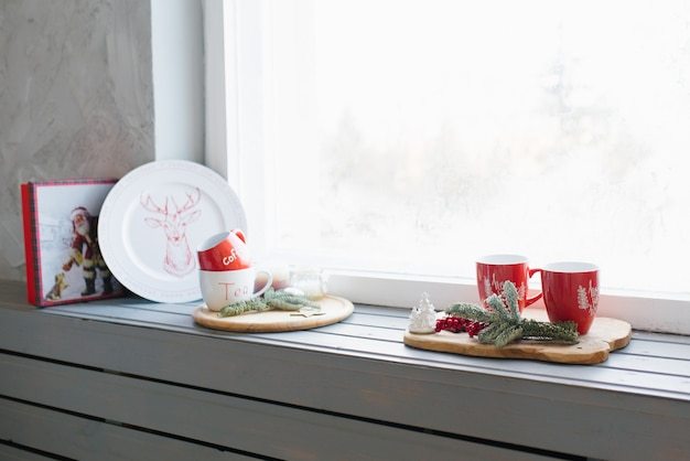 Red mugs with tea on the windowsill, christmas cozy decor