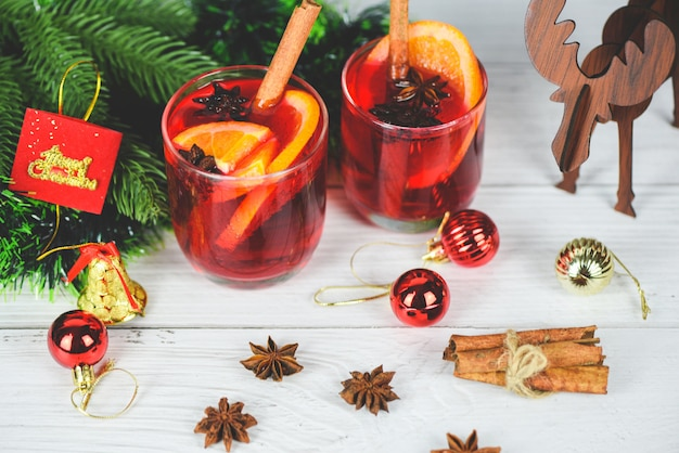 Red mulled wine glasses reindeer decorated table - christmas mulled wine delicious holiday like parties with orange cinnamon star anise spices for traditional christmas drinks winter holidays