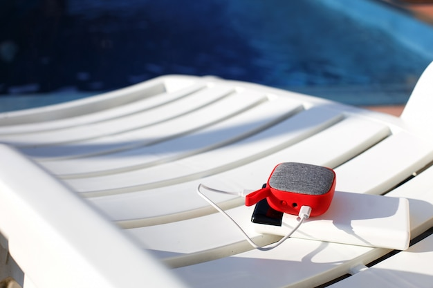 Red music portable speaker is charged from the power bank via usb on a deck chair near the pool.