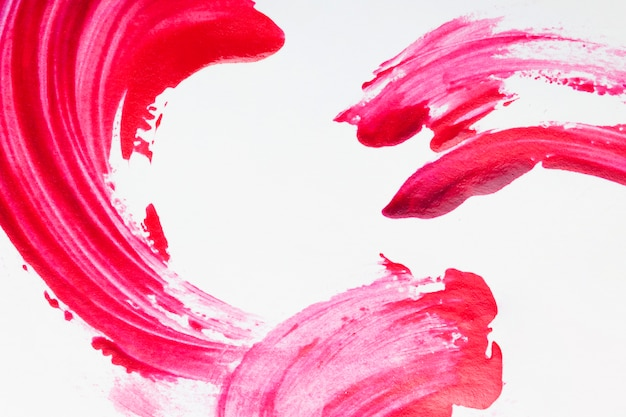 白い表面に分離された赤いマニキュアストローク