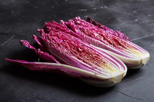 赤白菜(紫白菜)をダークストーンのテーブルで2つにカット。新鮮な野菜を調理する