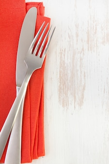 Red napkin with knife and fork on white