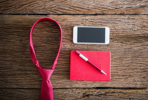 Красный галстук, ручка, записная книжка, смартфон на деревянном столе