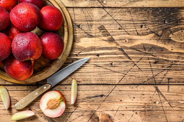 Red nectarines on a wooden tray and half a nectarine. wooden background. top view. copy space.