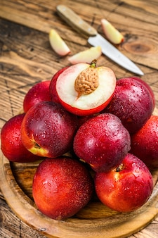 Red nectarines on a wooden tray and half a nectarine. wooden background. top view.