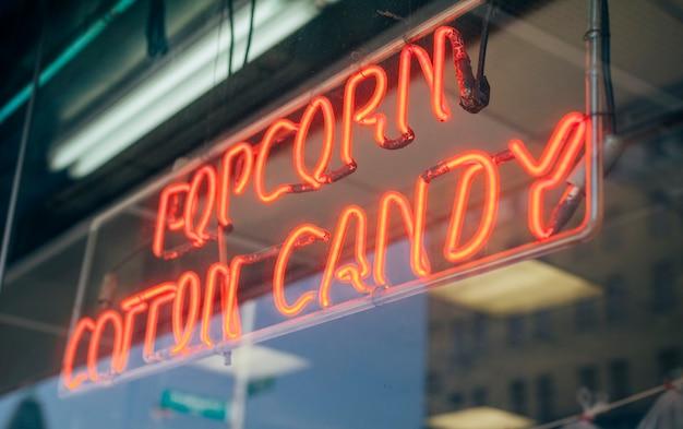 팝콘 솜사탕이라는 단어가 있는 쇼케이스의 빨간색 네온 사인