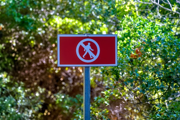 Red no walking sign for people in the forest