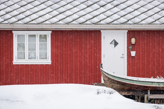 Red norwegian residence with wooden boat in blizzard on winter