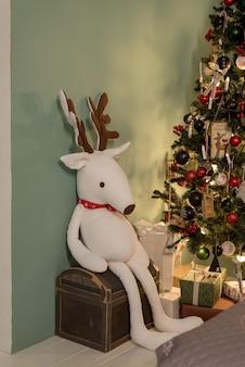 Рыжий олень. кукла с красноносым оленем сидит возле дерева. плюшевая кукла. игрушка плюшевый олень
