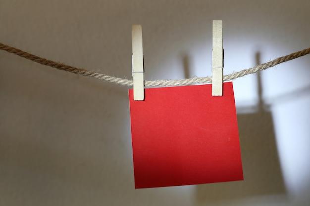 흰 벽에 밧줄에 매달려 빨간 메모 지.