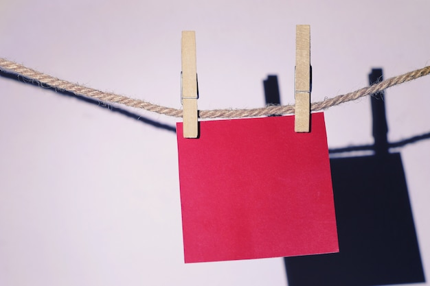 Red note paper hanging on rope on white wall.