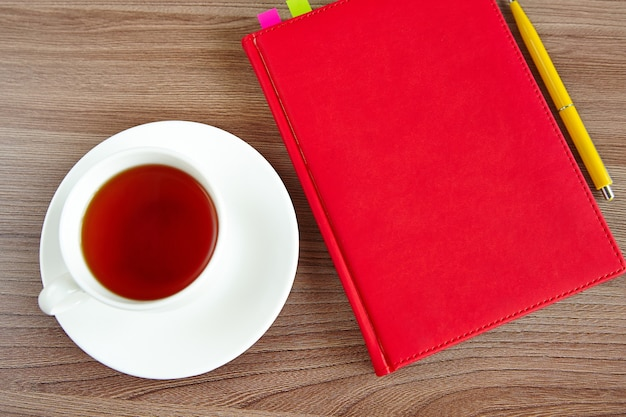 Red notebook and a cup of tea on a wooden table