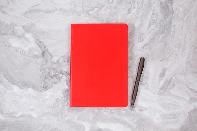 회색 대리석에 빨간색 노트북. 비즈니스, 사무 용품 또는 교육 개념 평면 누워