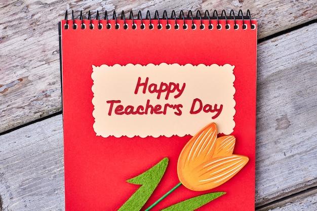 木製の表面に赤いノートブック。親愛なる先生のためのグリーティングカード。