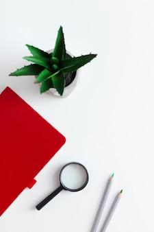 Красный блокнот, растение, смартфон, беспроводные наушники и карандаши на белом фоне