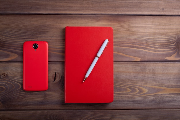 Red notebook and a smartphone.