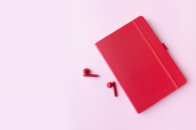Red notebook with wireless headphones on pink wall with copy space. minimal business concept