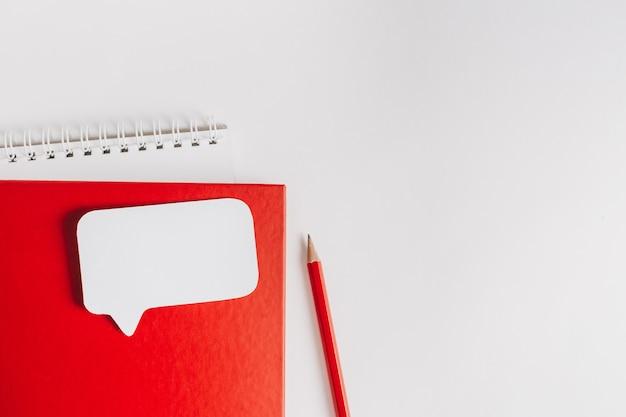 机の上の赤いメモ帳と白いステッカー。コピースペースのオフィスの表面にモックアップ