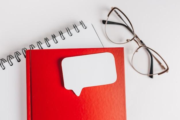赤いメモ帳、白いステッカー、机の上の眼鏡。コピースペースオフィスの背景でモックアップ。注意を忘れないことが重要です