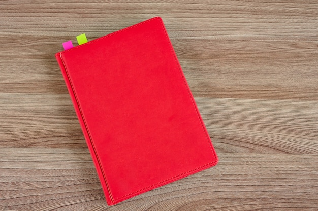 Red notepad with colored bookmarks on a wooden table