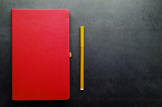 Red notepad with a marker on a black background, top view.