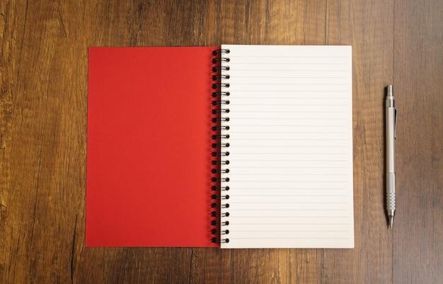 Notepad rosso con una penna vicino