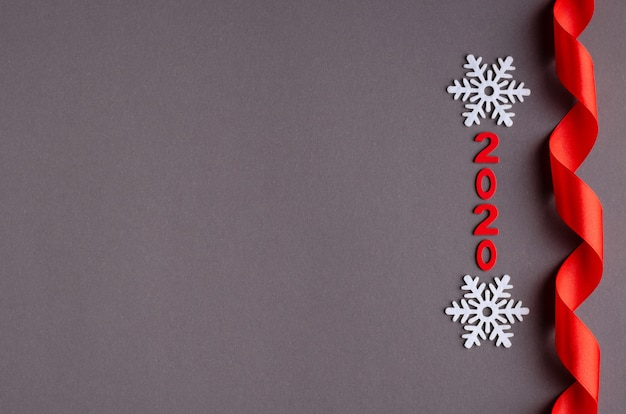 Red number 2020, ribbon and white snowflakes composition on dark background, new year and christmas holiday.