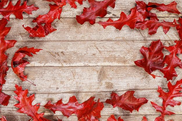 Красные дубовые листья на деревянном столе