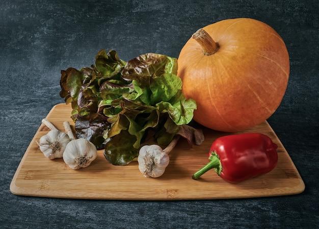 レッドオークサラダ、カボチャ、ニンニク、ピーマン、木の板に野菜、ヴィンテージスタイル