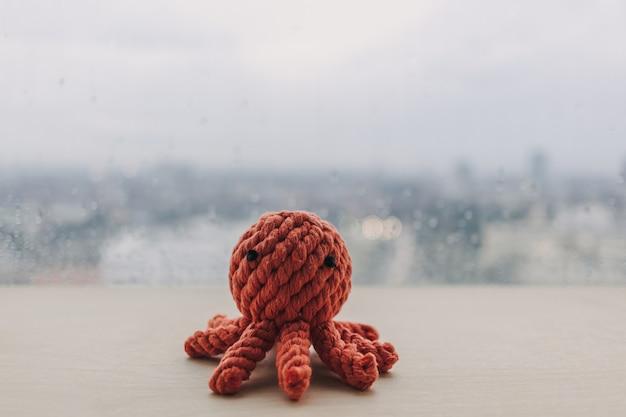 コピースペースのある木製の机の上で手作りのおもちゃの人形を編む赤いタコ