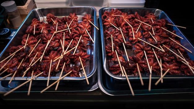 Красный осьминог с головой, фаршированной яйцом, - местная японская уличная еда в киото. маленькие осьминоги на палочках на рыночном прилавке в японии. японская кухня с закусками из морепродуктов