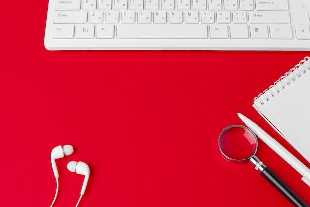 空白のノートブック、キーボード、消耗品、コピースペース、フラットレイアウトとトップビューで赤いオフィスデスクテーブル