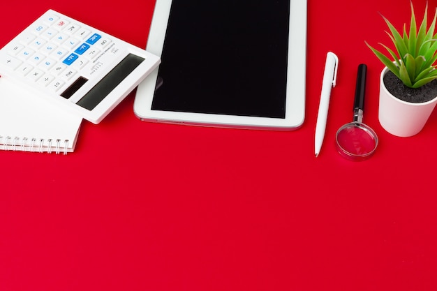 Red office desk table with blank notebook, keyboard and supplies. top view with copy space. flat lay.