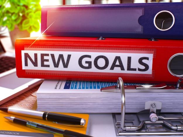 Красная папка офиса с надписью новые цели на рабочем столе офиса с канцелярскими принадлежностями и современным ноутбуком. бизнес-концепция новых целей на размытом фоне. новые цели - тонированное изображение. 3d.