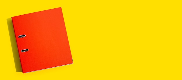 Red office folder on yellow background. top view