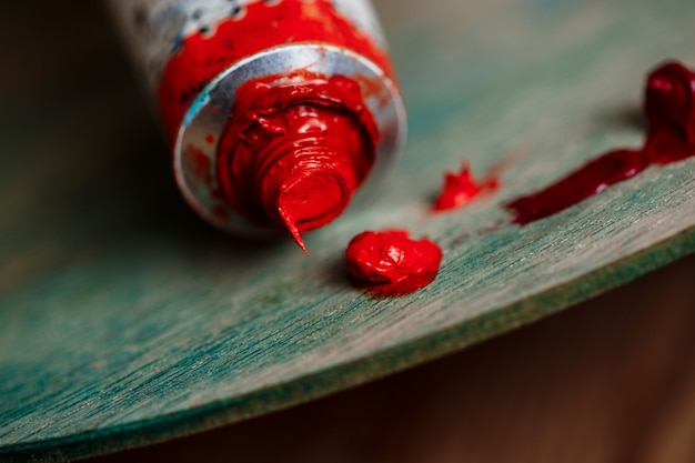 Red oil paint on palette over wood wall