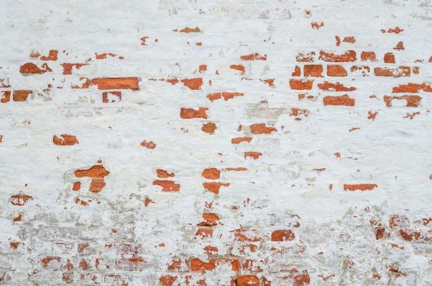 Красная старая выветренная кирпичная стена с битыми кусками побелки, шпатлевки и штукатурки