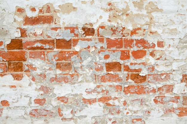 Red old weathered brick wall with beaten pieces of whitewash