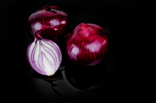 Red onion and half slice on black with reflect.