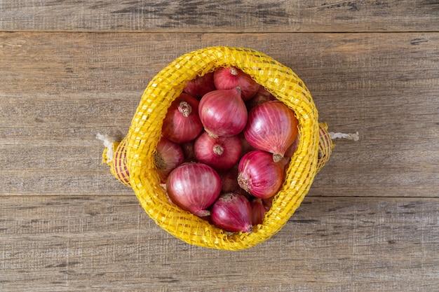 Красный лук на ветхой деревянной доске.