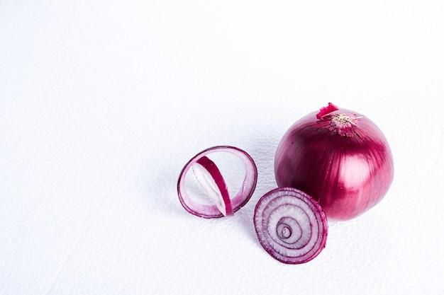 Cipolla rossa su un tavolo bianco, vista dall'alto.