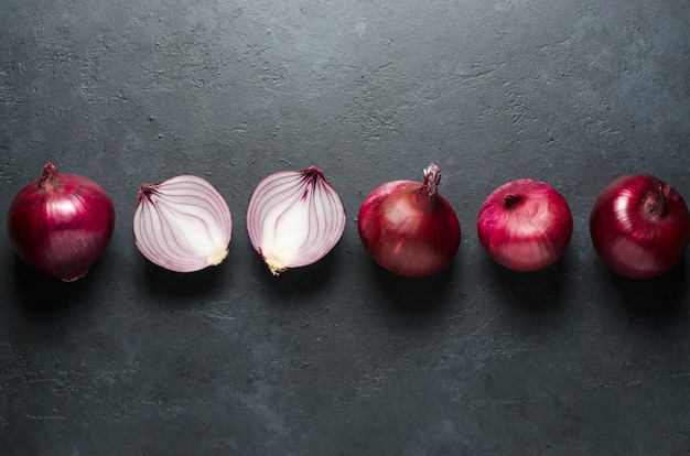 Red onion. whole and sliced onions. black background. flat lay, copy space