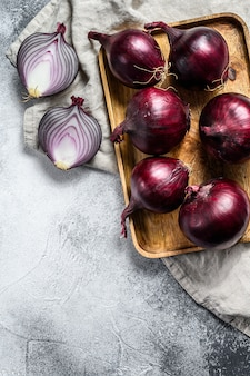 Red onion in a wooden bowl, onion halves. farm eco vegetables. gray background. top view
