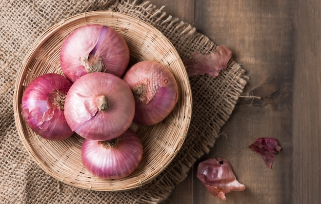 Red onions in bamboo basket and on wood background, vegetable for cooking food
