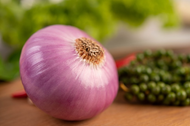 Red onions and fresh pepper on wooden table.