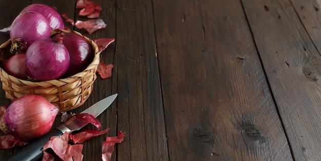 木製のテーブルの上の赤玉ねぎがクローズアップ