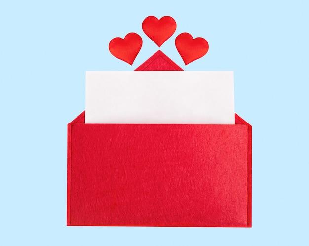 Красный открытый конверт с листом бумаги с сердечками на синем фоне. день святого валентина